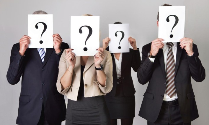 Business suits holding question marks